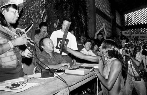 Índia TuÌra passa o terçado no rosto do diretor da Eletronorte JosÈ Antônio Muiniz Lopes durante o I Encontro da Nações IndÌgenas do Xingu. Em primeiro plano a esq. Pauliinho Paiakan Altamira, Pará, Brasil Foto Paulo Jares/Interfoto 1989.