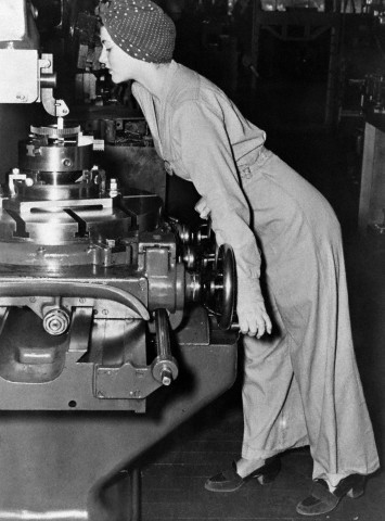 26 Mar 1942, Alameda, California, USA --- Pretty Naomi Parker is as easy to look at as overtime pay on the week's check. And she's a good example of an old contention that glamor is what goes into the clothes, and not the clothes. Pre-war fashion frills are only a discord in war-time clothing for women. Naomi wears heavy shoes, black suit, and a turban to keep her hair out of harm's way (we mean the machine, you dope). --- Image by © Corbis
